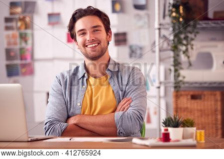 Portrait Of Smiling Male Student Or Business Owner Working In Fashion Using Laptop In Studio