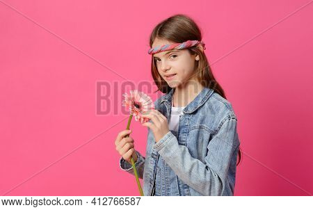 Teenager, 1 White Girl 10 Years Old In A Denim Shirt With A Pink Gerbera Flower In Her Hands On A Pi