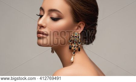 Beautiful Woman With Long Big Earrings. Beauty Girl With Elegant Hairstyle And Evening Make-up. Make