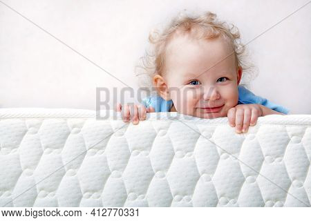 Baby On The Bed Mattress Close-up. The Sidewall Of The Mastras Is Stitched With Finishing Lines.