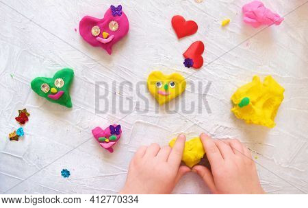 Child Playing With Colorful Modeling Clay With  Beads And Sequins And Sculpting Heart Figure. Home E