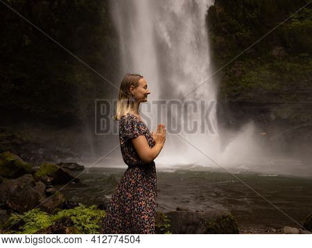 Young Caucasian Woman Spending Time Near Waterfall. Meditation And Relaxation. Hands In Namaste Mudr