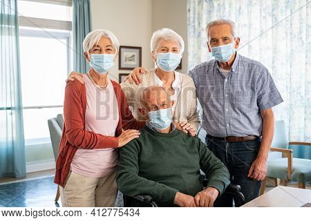 Portrait of senior men and women wearing protective face mask during the coronavirus epidemic at care facility centre. Group of seniors with disabled man wearing surgical mask while looking at camera.