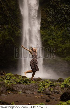 Happy Caucasian Woman Jumping Near The Waterfall. Legs In Motion Movement. Nature And Environment Co