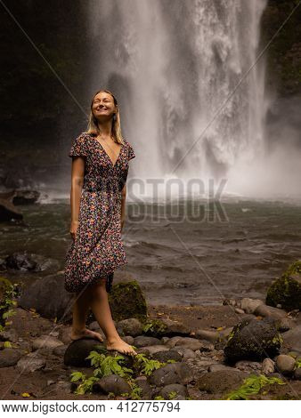 Young Caucasian Woman Walking In Tropical Forest Near The Waterfall. Nature And Environment Concept.