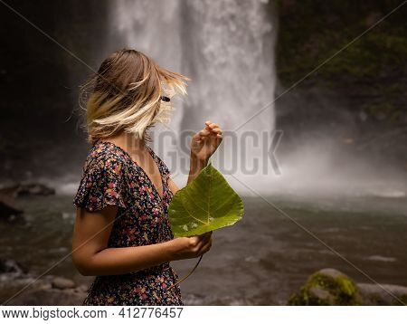 Caucasian Woman Holding Leaf, Enjoying Waterfall Landscape. Nature And Environment Concept. Travel L