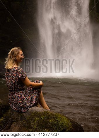 Young Caucasian Woman Sitting On The Rock And Enjoying Waterfall Landscape. Woman Portrait. Energy O