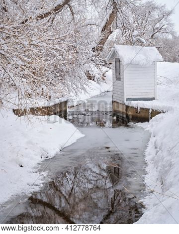 Boxelder Ditch diverting water from the Poudre RIver and water guage after heavy snowstorm in Fort Collins, northern Colorado