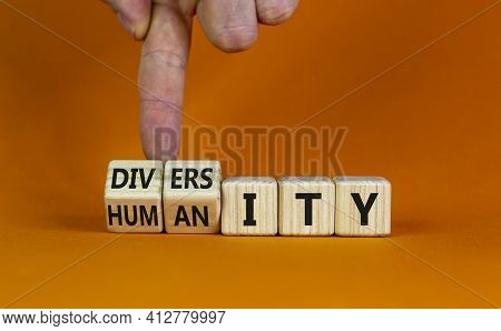 Diversity And Humanity Symbol. Businessman Turns Wooden Cubes And Changes The Word 'humanity' To 'di