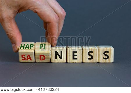 Happiness Or Sadness Symbol. Businessman Turns Cubes And Changes The Word 'sadness' To 'happiness'.