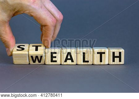 Stealth Wealth Symbol. Businessman Turns Wooden Cubes And Changes The Word 'wealth' To 'stealth'. Be