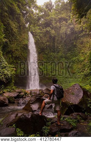 Asian Man Traveller Enjoying Waterfall Landscape In Tropical Forest. Man With Backpack. Energy Of Wa