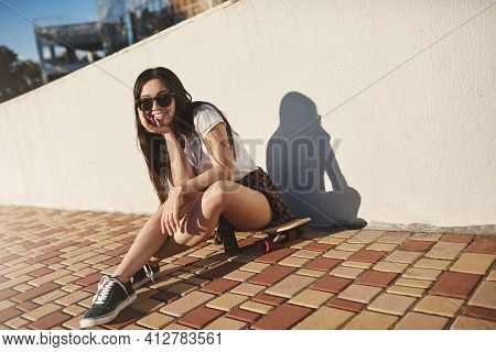 Side Action Shot Attractive Carefree Skater Girl In Hipster Outfit With Sunglasses Sit Near White Wa