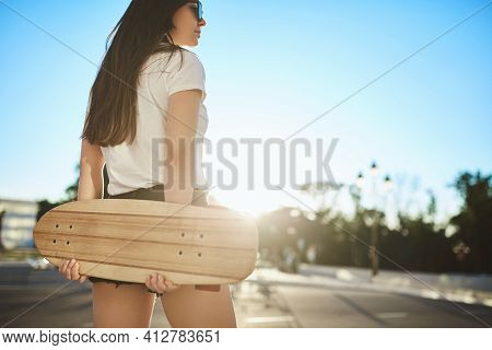 Low-angle Rear View Stylish Brunette Skater Girl Smiling Dreamy, Turn Head Right, Hold Wooden Penny