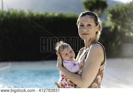 Happy Caucasian Mother With Imperfect Skin Holding Her Baby Girl In The Resort Garden Near The Swimm