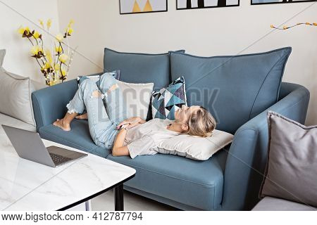 Unwell Young Beautiful Caucasian Woman Lying On Blue Sofa At Home, Touching Belly. Menstrual Period