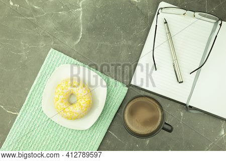 Round Donut In Chocolate On A White Plate. Donut Covered With White Chocolate And Sprinkled With Lem