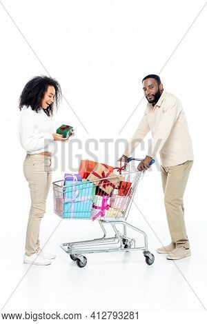 Joyful African American Woman Holding Present Near Husband And Shopping Trolley With Gift Boxes On W