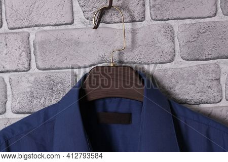 Blue Mens Shirt On Brown Plastic Hanger On Brick Gray Wall.