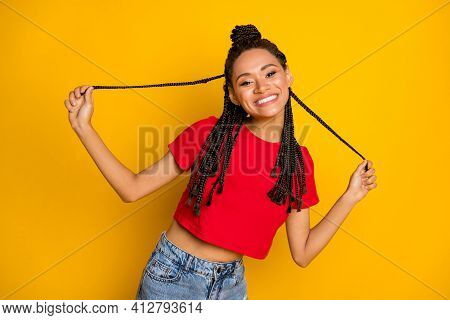 Portrait Of Pretty Glad Cheerful Girl Having Fun Pulling Hairdo Curls Isolated Over Bright Yellow Co