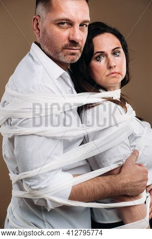 An Aggressive Man Embraces A Battered Woman And Is Wrapped In Bandages Together. Domestic Violence