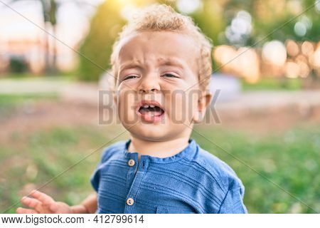 Cute and sad little boy crying having a tantrum at the park on a sunny day. Beautiful blonde hair male toddler frustrated with tears on face outdoors