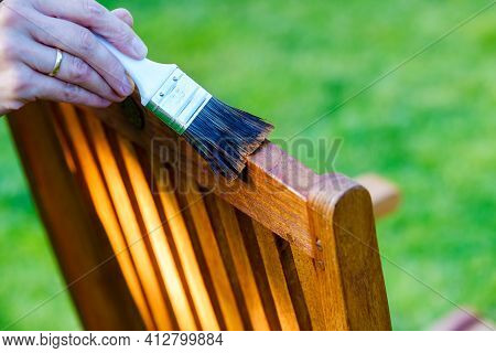 Female Hand Holding A Brush Applying Varnish Paint On A Wooden Garden Chair- Painting And Caring For