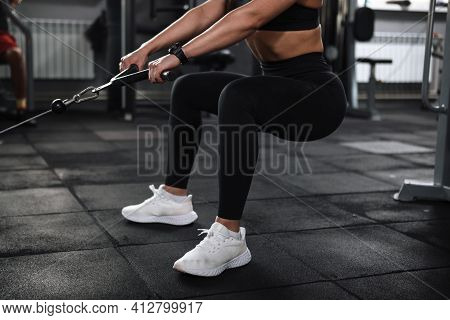 Cropped Shot Of Unrecognizable Sportswoman With Toned Sexy Body Squatting In Crossover Gym Machine