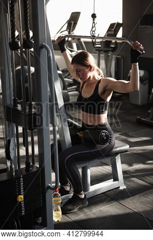 Vertical Shot Of A Sportswoman Exercising On Lat Pull Down Machine At The Gym