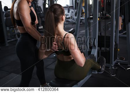 Cropped Shot Of Athletic  Fit Woman Doing Back Muscles Exercise With Her Personal Trainer