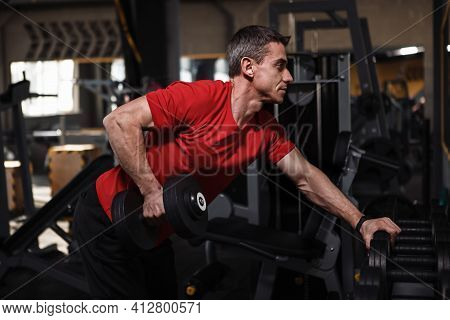 Middle Aged Sportsman Lifting Weights At The Gym