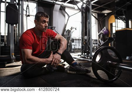 Mature Sportsman Resting On Gym Floor After Exercising With Heavy Barbell, Copy Space