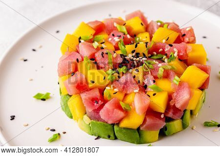 Tuna Mango Avocado Salad Tartare Served With Green Onions And Sesame Seeds.