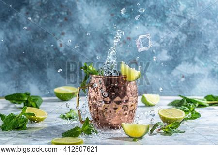 Cold Moscow Mules Cocktail With Ginger Beer, Vodka, Lime. Splashes And Ice Frozen Motion.