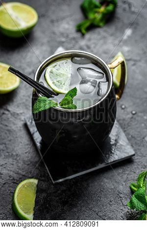 Lime Moscow Mule Alcohol Cocktails With Fresh Mint And Ice In Copper Mugs On Black Background, Top V