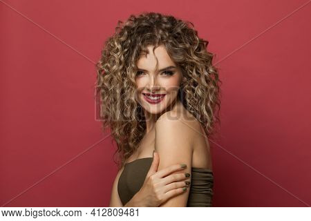 Pretty Smiling Woman With Long Healthy Curly Hair On Red Background. Pretty Model With Trendy Stylin