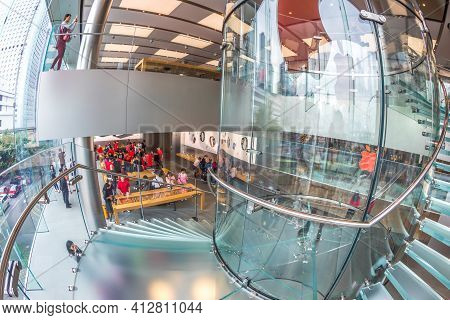 Hong Kong, China - December 4, 2016: Fish-eye Ground View Of Red Apple Sign And Glass Spiral Stairwa