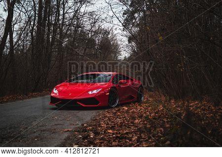 Kyiv, Ukraine - November 2019. Red Italian Supercar Lamborghini Huracan In The Autumn Forest.