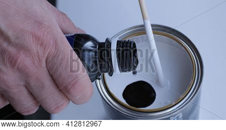 Adding Black Color From A Plastic Bottle To A Tin Can With White Paint To Obtain The Desired Gray Sh