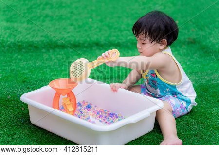 Asian Preschool Baby Uses An Orange Toy Sieve To Scoop Rainbow Beads And Play With Water Cone That I