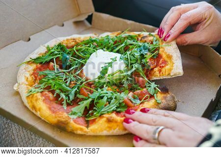 A Woman Sits In A Car And Tears Pizza With Burrata Cheese And Greens With Red Lacquered Nails