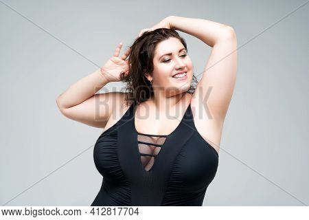 Sexy Plus Size Fashion Model In Black One-piece Swimsuit, Fat Woman In Lingerie On Gray Background