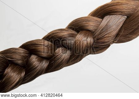 .a Braid Of Chestnut-colored Hair. The Braid Is Made Of Dark Brown, Thick Hair. On A White Backgroun