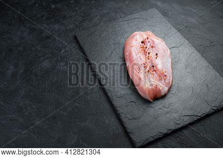 Fresh, Raw Meat On A Black Background. A Serving Piece Of Turkey Fillet. Side View With Copy Space.