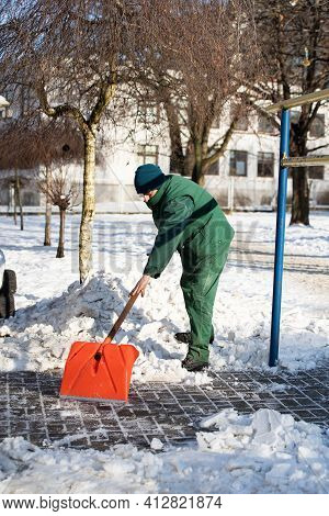 The Landlord Scrapes Snow And Ice With An Orange Cobblestone Shovel