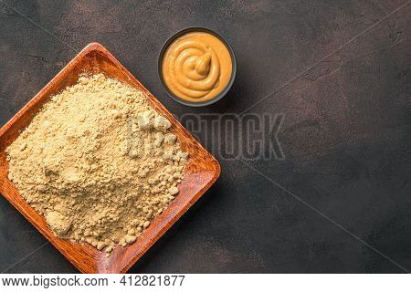 Ready-made Mustard And Mustard Powder On A Brown Concrete Background. Minimalistic Culinary Backgrou