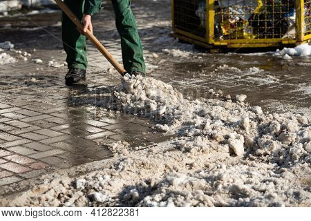A Manual Worker Scrapes Snow Off The Pavement With A Metal Shovel