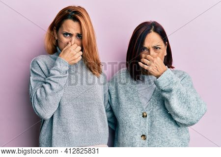 Latin mother and daughter wearing casual clothes smelling something stinky and disgusting, intolerable smell, holding breath with fingers on nose. bad smell