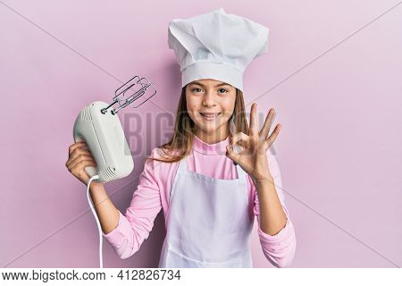 Beautiful brunette little girl wearing chef hat holding pastry blender electric mixer doing ok sign with fingers, smiling friendly gesturing excellent symbol