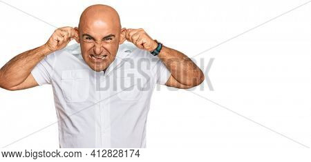 Mature middle east man with mustache wearing casual white shirt smiling pulling ears with fingers, funny gesture. audition problem